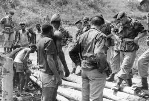 Zaire/Congo: Belgium paratroopers and Congolese men building a wooden bridge
