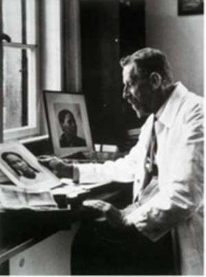 The evil Dr. Eugen Fischer whose pseudo-scientific theories of racial purity were practised on Namibians, at his desk with photos of African women.