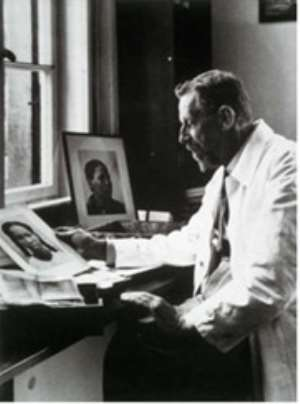 The evil Dr.Eugen Fischer whose pseudo-scientific theories of racial purity were practised on Namibians at his desk with photos of African women.
