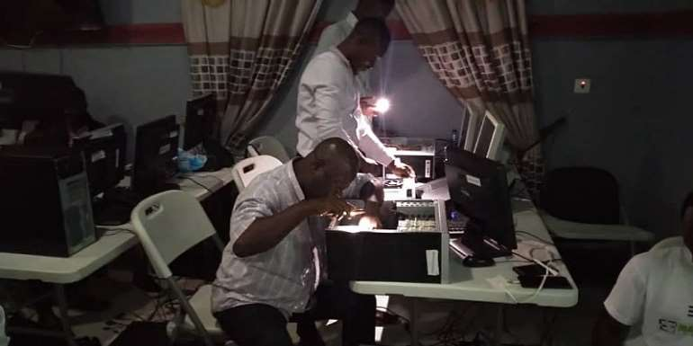 """Photo: A Teacher is practicing a """"Whatsapp surgery"""" with his phone during desktop repair, this August in Eastern Region."""