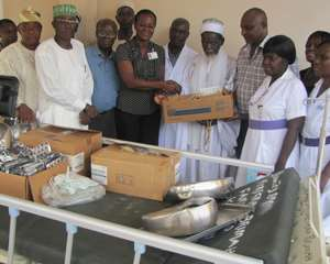 Sheikh Osman Nuhu Sharubutu presenting the medical equipment to Dr. Ivy Ekem as a representative of the family and others look on.