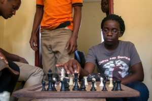 18-year-old Phiona Mutesi plays a game of chess with her colleagues at the chess academy in Kibuye, Kampala, on January 26, 2015