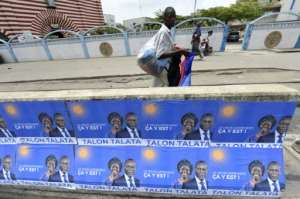 Talon, seen here with his running mate Mariam Talata on campaign posters in Cotonou, is expected to win on Sunday.  By PIUS UTOMI EKPEI (AFP)