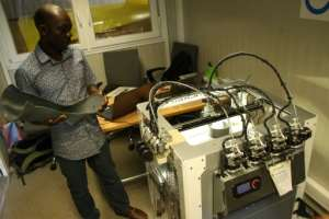 Technician Fabrice Agbelehounko Djodji checks the work of a 3D printer used to produce prosthetic supports at the African Organisation for the Development of Centres for Disabled People in Lome. Making 3D devices locally is expected to cut costs..  By MATTEO FRASCHINI KOFFI (AFP)