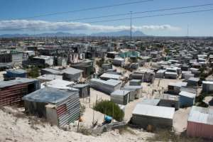 The corrugated-iron shacks typically house between three and seven people -- hot, cramped conditions that are made even worse by the lockdown.  By RODGER BOSCH (AFP)