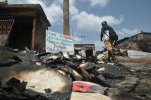 The aftermath of violence in the central Ivorian town of Toumodi. The sign says: 'Youth of Toumodi, you burn shops, restaurants, markets... tomorrow, how do we get by?'. By SIA KAMBOU (AFP)