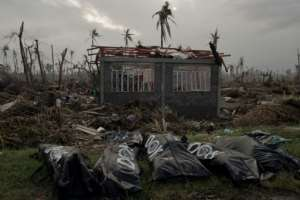 The bodies of five victims of typhoon Haiyan lie in front of a damaged house in Tanauan on November 20, 2013 in the Philippines.  By NICOLAS ASFOURI (AFP/File)