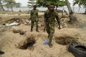The ground is pockmarked with holes where residents have dug down to pipelines, some filled with shiny oil and water.  By PIUS UTOMI EKPEI (AFP)