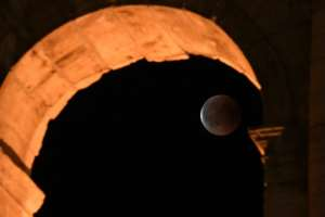 The full moon during a 'blood moon' eclipse behind the ancient Colosseum in Rome in July, 2018.  By Tiziana FABI (AFP/File)