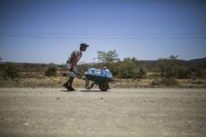The hot way home: A young man pushes a wheelbarrow with bottles filled with water.  By Guillem Sartorio (AFP)