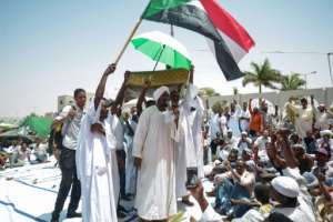 The imam is draped in the Sudanese flag as he leads Friday prayers at the army sit-in. By MOHAMMED HEMMEAIDA (AFP)
