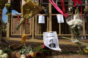 The murder that changed everything: A picture of 19-year-old university student Uyinene Mrwetyana is attached to a barrier at Clareinch Post Office in Cape Town, where she was killed.  By RODGER BOSCH (AFP)