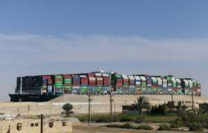 The MV Ever Given's huge cargo of containers towers over its superstructure in this photograph taken from the adjacent desert after it resumed its journey through the Suez Canal.  By Ahmad HASSAN (AFP)