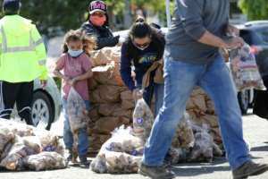 The Reed family in Pasco, Washington, hands out potatoes donated by Washington famers who are giving away a million pounds of excess stock they have as a result of the food service industry slowdown.  By Jason Redmond (AFP)
