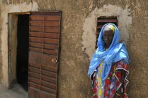 This government handout picture shows a woman standing outside a house in the village near Mopti that was attacked on Saturday. By Handout (MALIAN PRESIDENCY/AFP)
