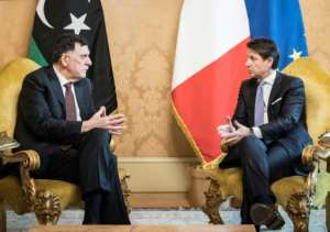 This photo handed out on January 11, 2020 by the Palazzo Chigi Press Office shows Italian Prime Minister Giuseppe Conte (R), who said Italy would make an