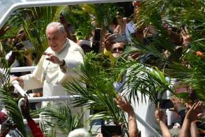 Throngs of cheering faithful waving palm fronds lined the streets of Port Louis as the popemobile shuttled the Argentine pontiff to the hilltop Mary Queen of Peace Monument.  By Tiziana FABI (AFP)