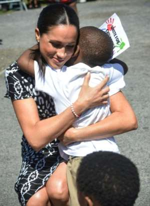 Time for a hug: 'I am here as a mother, a wife, a woman of colour and your sister,' Meghan told the cheering crowd.  By Courtney AFRICA (POOL/AFP)