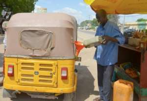 Time for a top-up: A taxi driver in Maradi buys petrol smuggled across the border from Nigeria, where the fuel is heavily subsidised.  By BOUREIMA HAMA (AFP)