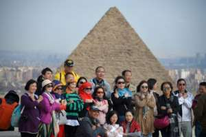 Tourists pose for a group picture at the Giza pyramids  on the southwestern outskirts of the Egyptian capital Cairo on December 29, 2018.  By MOHAMED EL-SHAHED (AFP)