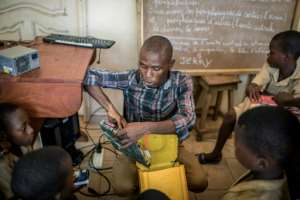 Trainer Raoul Letchede shows the kids the components they will use to assemble a makeshift computer in a 25-litre plastic container. By Yanick Folly (AFP)
