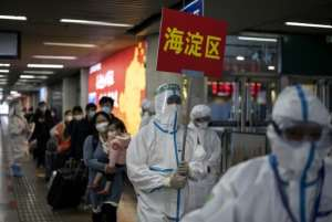 Transport personnel wearing hazmat suits guide travellers arriving from Wuhan to buses, which will take them to their quarantine locations, at Beijing West Railway Station.  By Noel CELIS (AFP)