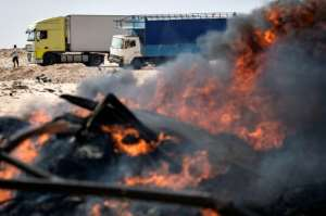 Trucks behind burning waste on a road between Morocco and Mauritania in Guerguerat.  By Fadel SENNA (AFP)