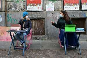 Two 12-year-olds sit in front of Italo Calvino school in Turin as they protest against school closures because of government restrictions over the Covid-19 pandemic.  By Miguel MEDINA (AFP)