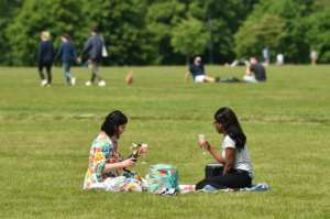 Two women enjoy a drink in the grass in London's Hyde Park, opened for the first time in months.  By Glyn KIRK (AFP)