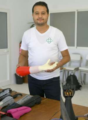 Tunisian engineer Mohamed Dhaouafi, who launched his start-up in 2017 from his parents' home, holds a prototype of an artificial hand.  By Bechir TAIEB (AFP)