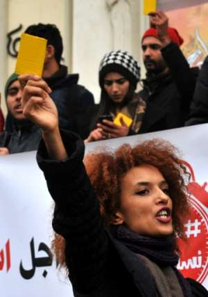 Tunisian protesters wave yellow cards and shout slogans outside the governorate's offices in Tunis during a demonstration over price hikes and austerity measures on January 12, 2018