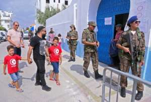 Tunisian soldiers stand guard outside a polling station as voters arrive to cast their ballots in Sousse on Sunday.  By ANIS MILI (AFP)