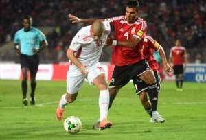 Tunisia's Wahbi Khazri (L) is marked by Libya's Mohamed Al Ghanodi (R) during a World Cup qualification football match at Rades Olympic Stadium in Tunis on November 11, 2017