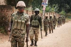 Ugandan troops pictured on Monday near the street leading to Bobi Wine's home.  By YASUYOSHI CHIBA (AFP)