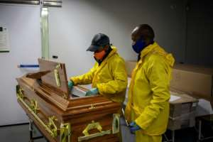 Undertakers clad in masks and protective suits check the coffin containing Motlhabane's remains. By Michele Spatari (AFP)
