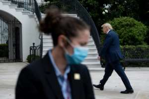 US President Donald Trump walks from Marine One to the White House as a secret service agent wearing a face mask looks in Washington, DC.  By Brendan Smialowski (AFP)