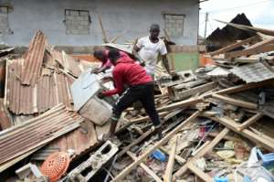 Victims try to salvage belongings trapped in the rubble of a house destroyed by the explosion.  By PIUS UTOMI EKPEI (AFP)