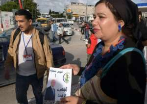 Volunteers distribute photos of Tunisian conservative law professor and presidential candidate Kais Saied, one of two political outsiders in Sunday's election runoff.  By FETHI BELAID (AFP)