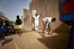 With the schools closed, Malian children find other diversions like marbles to pass the time.  By MICHELE CATTANI (AFP)