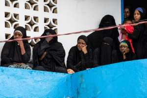 Women watch on from a balcony as bodies are taken away from the site of the fire on Thursday.  By Carielle DOE (AFP)