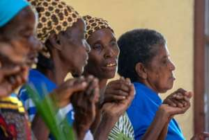 Women join hands in worship during the service.  By Zinyange AUNTONY (AFP)