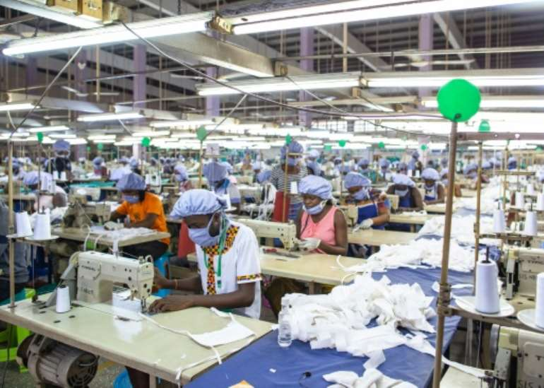 Workers sew personal protective equipment in Ghana, which has lifted a coronavirus lockdown that hit the poor hard.  By Nipah Dennis (AFP)