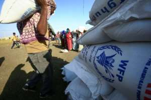 Workers unload World Food Programme food aid at the 'Village 8' reception facility on Friday.  By ASHRAF SHAZLY (AFP)