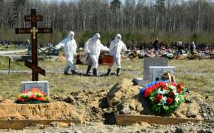 Workers wearing protective gear bury a coronavirus victim at a cemetery on the outskirts of Saint Petersburg.  By OLGA MALTSEVA (AFP)