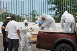 Workers wrap with plastic a coffin with the remains of a person who died from the coronavirus, COVID-19 in Guayaquil, Ecuador.  By Jose Sánchez (AFP)