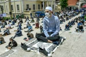 Worshippers wearing face masks maintain the required social distance during Friday prayers outside The Fatih Mosque in Istanbul on May 29.  By BULENT KILIC (AFP)
