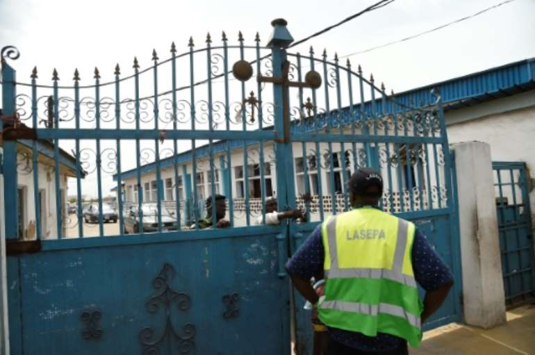 Worshippers clustered at the gate of Makoko's Celestial Church of Christ only to find policemen handing out fliers on the dangers of the virus. By PIUS UTOMI EKPEI (AFP)