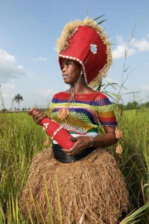 Yealie Kabba, a Bondo society member in Waterloo, wears a red hat with a mirror called a kashak and holds a red bottle filled with spiritual wine, used for purification.  By LYNN ROSSI (AFP)