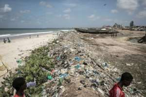 Young Senegalese walk through rubbish piled up along the coastline in Bargny.  By JOHN WESSELS (AFP)