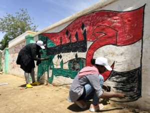Young Sudanese paint a national flag on a wall in the capital Khartoum.  By ASHRAF SHAZLY (AFP)
